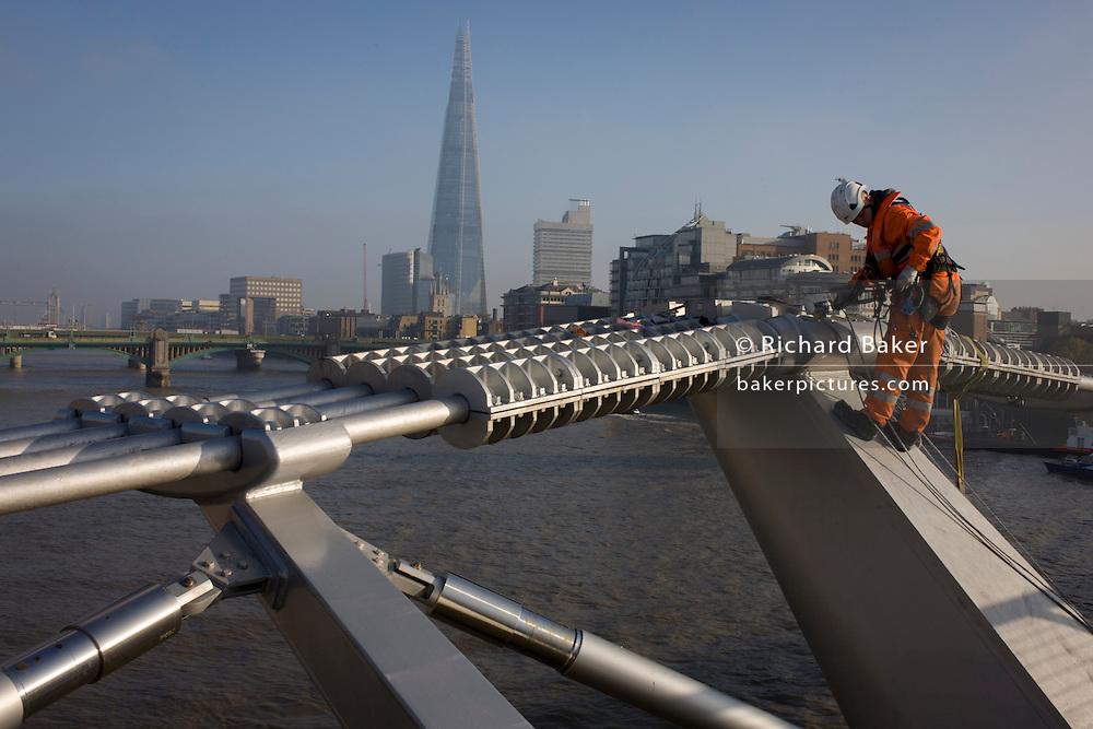 With the Shard in the background, a cleaning crew with the contractor Conroy wash down surfaces on the Millennium Bridge for the first time in its 15 year history. With the Shard in the background, a cleaning crew with the contractor Conway wash down surfaces on the Millennium Bridge for the first time in its 15 year history.