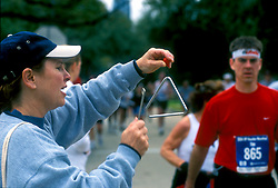 Stock photo of a woman hitting a triangle as a signal