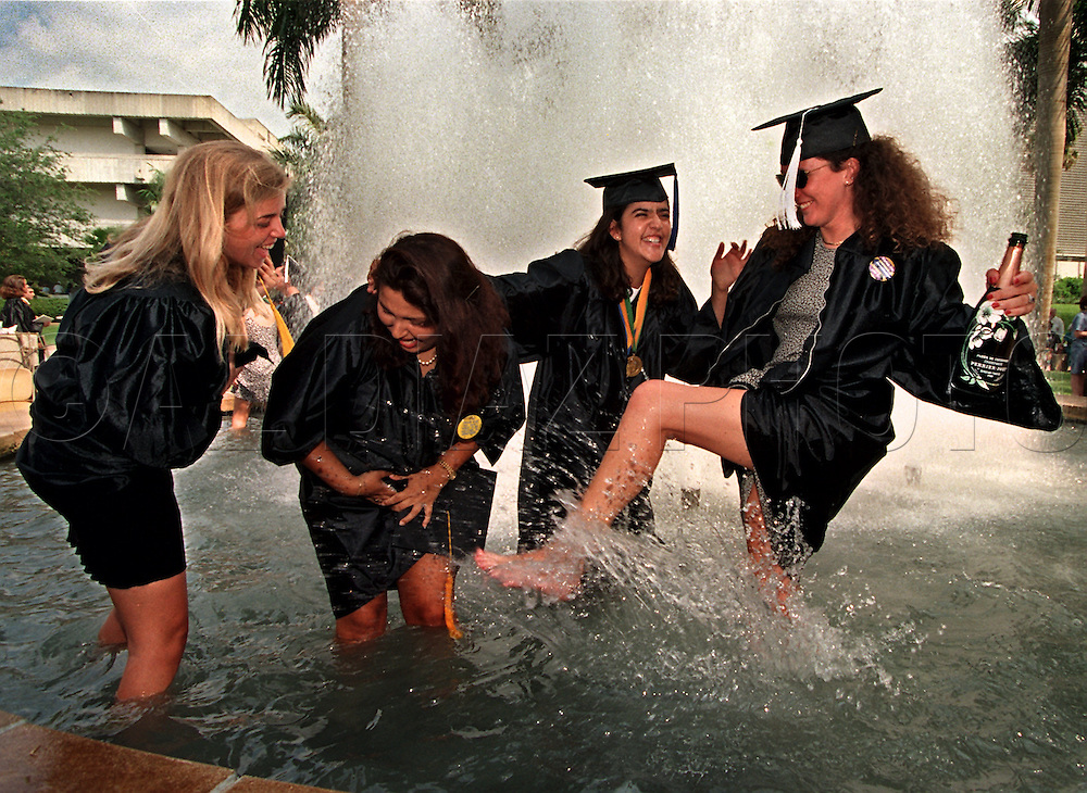 University of Miami graduates, Melissa Koester, 21, Claudia Orbego, 20, Camila Cote, 21, Leslie Kovar, 21, jump into a water fountain on campus after commencement ceremonies.