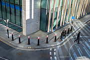 Reflected sunlight leaves lines and curves in an aerial cityscape, on the corner of a City of London street where offices are still largely empty as workers work from home during the third lockdown of the Coronavirus pandemic, on 9th March 2021, in London, England.