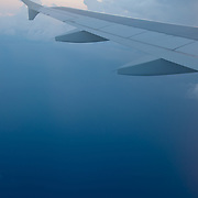 View from the plane: deep blue ocean and the cloud on the sky