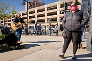 31 OCTOBER 2020 - DES MOINES, IOWA: RANDY KONG, a Des Moines busker, performs for people in line to vote at the Polk County Auditor's Office in Des Moines. This is the last weekend of early voting before the 2020 US presidential election. An elections official said that by November 3, which is Election Day, about 45 percent of the registered voters in Polk County will have already voted.    PHOTO BY JACK KURTZ