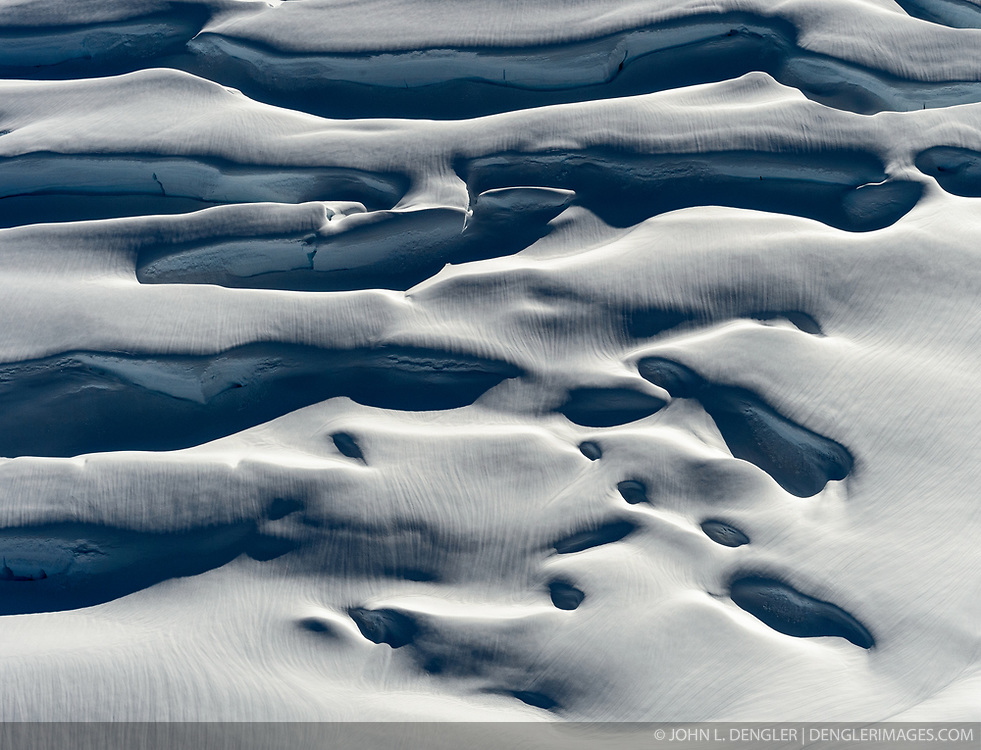 Deep crevasses of Margerie Glacier take on an other worldly look in early evening light in this photo taken at the uppermost region of the glacier just inside the U.S. at the Canadian border. The 21-mile-long glacier in Glacier Bay National Park and Preserve is one of the park's tidewater glaciers. <br /> <br /> Glacier Bay National Park is located in southeast Alaska. Known for its spectacular tidewater glaciers, icefields, and tall costal mountains, the park is also an important marine wilderness area. The park a popular destination for cruise ships, is also known for its sea kayaking and wildlife viewing opportunities. <br /> <br /> Glacier Bay National Park is home to humpback whales which feed in the park's protected waters during the summer, both black and grizzly bears, moose, wolves, sea otters, harbor seals, steller's sea lions and numerous species of sea birds. <br /> <br /> The dynamically changing park, known for its large, contiguous, intact ecosystems, is a United Nations biosphere reserve and a UNESCO World Heritage site.