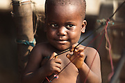 A boy plays with strings in the West Point slum of Monrovia, Montserrado county, Liberia on Monday April 2, 2012.