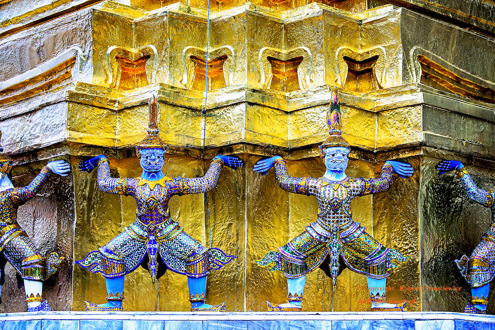 Stupa Support: Blue faced, Demon monkey statues are dressed in a multi coloured traditional dress made of coloured mirrors and squat in front of and appear to hold up a golden Stupa, Imperial Grand Palace in Bangkok Thailand.