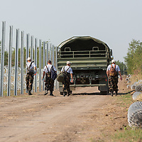 Workers inspect construction in progress as a second line of border fence is being built behind a NATO barbed wire fence to stop illegal migrants entering on the green border between Serbia and Hungary near Asotthalom (about 190 km South of capital city Budapest), Hungary on August 13, 2015. ATTILA VOLGYI