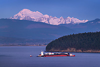 Oil tanker in  Fidalgo Bay being towed to March Point Refinery, Anacortes washington. Mount Baker is in the Distance.
