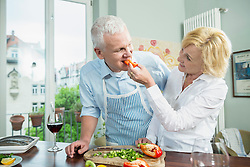 Mature woman feeding food to mature man, smiling