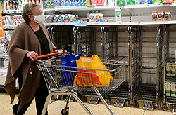 © Licensed to London News Pictures. 27/08/2021. London, UK. A shopper walks past nearly empty shelves of fresh milk in Sainsbury's, north London. UK food producers and supermarkets are warning that empty shelves could continue unless the government acts to resolve the shortage of workers and lorry drivers, caused by Brexit and the coronavirus pandemic. Photo credit: Dinendra Haria/LNP