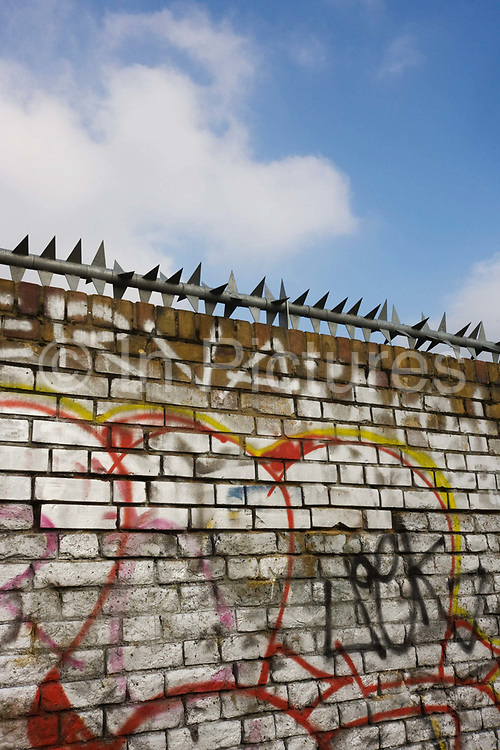Dated October 2010 with less than two years before the London Olympiad commenced, we see a section of the outer fence to the Olympic Park. The brick wall marks the boundary of no access to land near River Lea in East London. Sharp barbs of security wall line the top, keeping out trespassers.  Covered in graffiti, it describes more the outer limit of the the property secured by the Olympic Authority who purchased land from small industrial businesses and landowners, separating people from their own localities - all in the name of a three-week sporting event that few feel they would benefit from.
