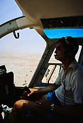Oil industry Saudi Arabia, helicopter Bell 206 JetRanger 1979 pilot in cockpit flying over desert