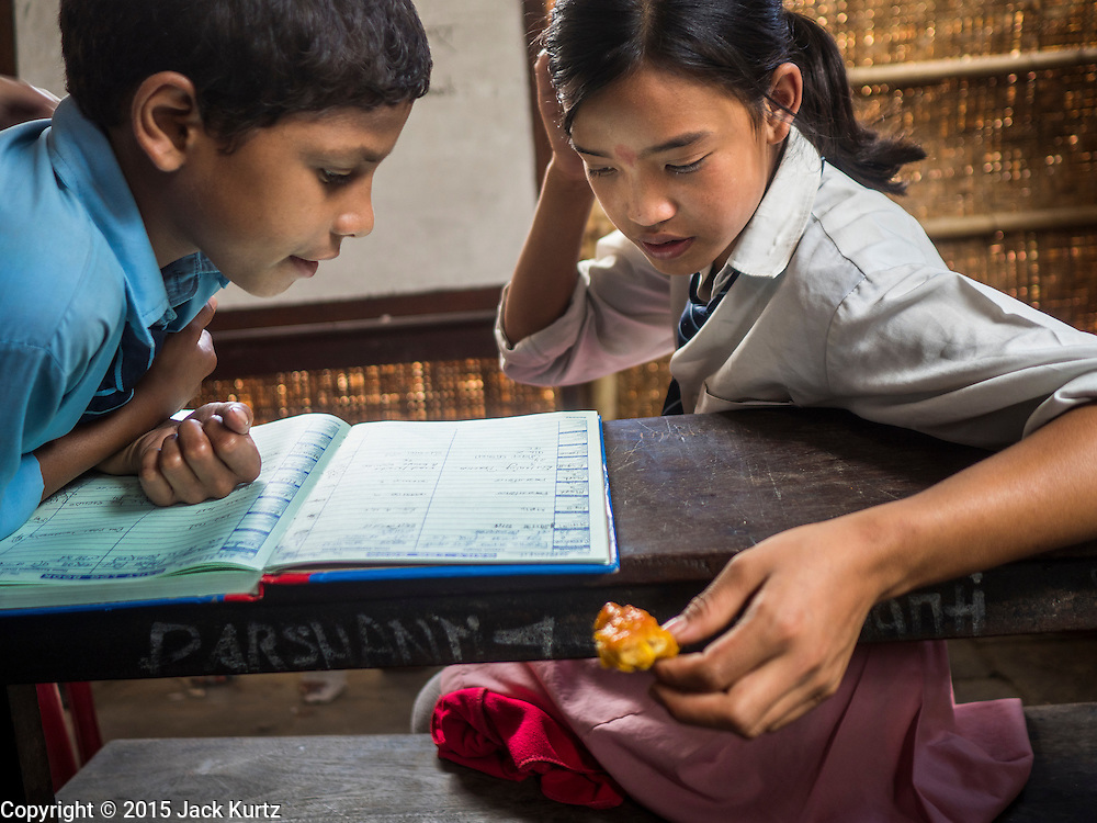 03 AUGUST 2015 - KATHMANDU, NEPAL:  A boy and girl study in a temporary school in central Kathmandu. Parts of her existing school were damaged in the earthquake and officials are afraid to use the existing structure, so they have set up a temporary school made of woven matting. The Nepal Earthquake on April 25, 2015, (also known as the Gorkha earthquake) killed more than 9,000 people and injured more than 23,000. It had a magnitude of 7.8. The epicenter was east of the district of Lamjung, and its hypocenter was at a depth of approximately 15km (9.3mi). It was the worst natural disaster to strike Nepal since the 1934 Nepal–Bihar earthquake. The earthquake triggered an avalanche on Mount Everest, killing at least 19. The earthquake also set off an avalanche in the Langtang valley, where 250 people were reported missing. Hundreds of thousands of people were made homeless with entire villages flattened across many districts of the country. Centuries-old buildings were destroyed at UNESCO World Heritage sites in the Kathmandu Valley, including some at the Kathmandu Durbar Square, the Patan Durbar Squar, the Bhaktapur Durbar Square, the Changu Narayan Temple and the Swayambhunath Stupa. Geophysicists and other experts had warned for decades that Nepal was vulnerable to a deadly earthquake, particularly because of its geology, urbanization, and architecture.    PHOTO BY JACK KURTZ