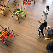 Nederland Rotterdam 4 juni 2008 20080604 Foto: David Rozing .VMBO leeringen van brede school Nieuw Zuid aan de Putsebocht in Rotterdam doen corvee werkzaamheden in de aula / maken de aula schoon  .De brede school is - in Nederland - een definitie voor de samenwerkende partijen die zich bezighouden met opgroeiende kinderen. Hierbij hoort in ieder geval onderwijs en welzijn, maar vaak ook kinderopvang, cultuur, sport, de bibliotheek, enz. In de praktijk is de brede school een plaats waar school en voor- en naschoolse opvang in elkaar samenvloeien..De brede school is een samenwerkingsverband tussen partijen die zich bezighouden met opgroeiende kinderen. Doel van het samenwerkingsverband is de ontwikkelingskansen van de kinderen te vergroten. Een ander doel kan zijn een doorlopende, en op elkaar aansluitende opvang te bieden. .De Brede School is geen nieuw begrip meer in Rotterdam. Sinds een aantal jaar breidt een groot aantal onderwijsinstellingen in het primair- en voortgezet onderwijs in Rotterdam het lesprogramma meer en meer uit met een keur aan activiteiten. Dit kunnen activiteiten zijn die zich richten op sociaal-emotionele, fysieke en cognitieve ontwikkeling van leerlingen, maar ook buiten- of voorschoolse activiteiten die de integratie en participatie van leerlingen en ouders bevorderen..Scholen werken samen met verschillende partners (organisaties, verenigingen, etc.) uit de buurt. Op deze manier sluiten binnen- en buitenschoolse activiteiten zo veel mogelijk op elkaar aan. Het doel? Om leerachterstanden te voorkomen en op te heffen, leer- en ontwikkelingsmogelijkheden te vergroten en de leerprestaties van leerlingen te verbeteren. En belangrijk: dat leerlingen kunnen ervaren waar ze aanleg voor hebben en hun talenten verder ontwikkelen. alle Brede Scholen in het Primair Onderwijs in Rotterdam per 1 januari 2007 verplicht voor-, tussen- en naschoolse opvang moeten aanbieden tussen 07.30 uur en 18.30 uur. Dit kan weer belangrijke gevolgen hebben voor het ontwik