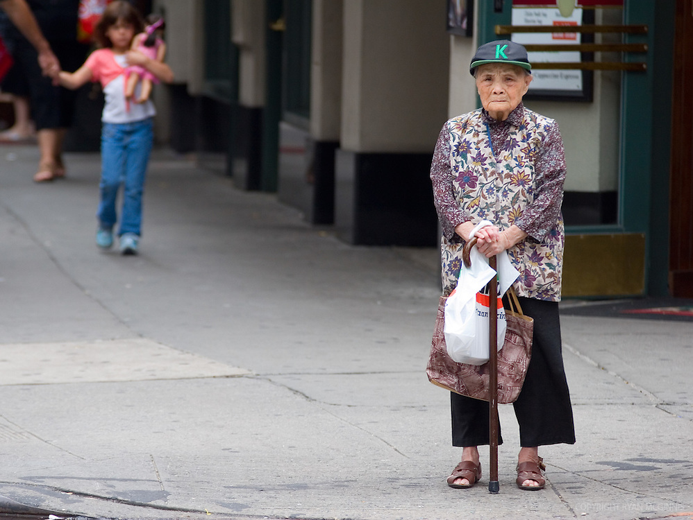 Candid of a woman waiting to cross the street, Chinatown, New York City, August 15, 2006.