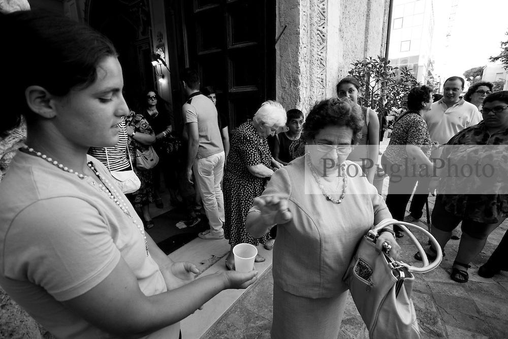 Fedeli all'uscita dalla chiesa dell'Arcangelo Michele, situata in Mesagne (Br), che offrono pochi spiccioli a delle ragazzine rom. La foto è stata scattata durante la celebrazione della Madonna del Carmine protettrice del paese, il 15-07-2010.