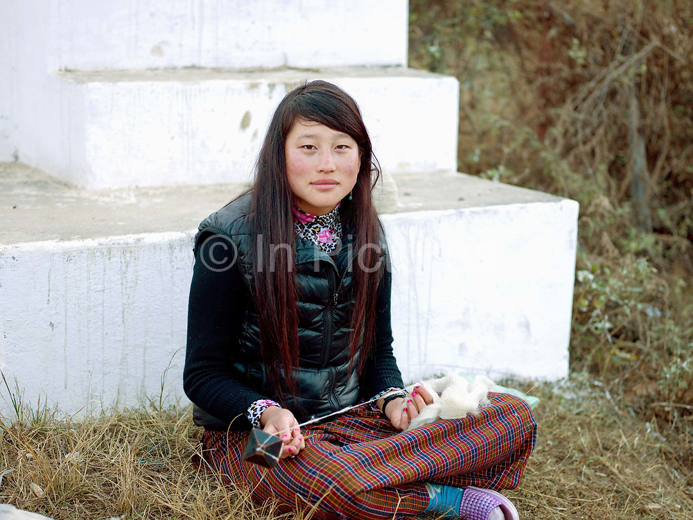 A young Layap woman from Laya spins sheep wool using a drop spindle called a Yoekpa, Punakha, Western Bhutan. The Layap are inhabitants of the northernmost region of Bhutan. Traditionally, their clothes are woven from yak hair and wool although the younger women often wear the kira, the Bhutanese national dress. They are a semi-nomadic tribe whose source of livelihood is dependent on yaks and sheep the products of which they barter with the people of Punakha for daily necessities. Given the geographic isolation of many of Bhutan's villages, there are 16 different dialects and 14 regional groups in the country. Many tribes have kept alive their distinct cultural identities through their dress, language and traditions over the years.
