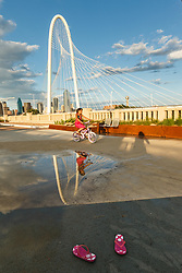 Girl on bike near puddle and pink flip flops. On Continental Avenue Bridge with Margaret Hunt Hill Bridge in background, Trinity River, Dallas, Texas, USA.