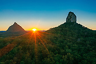 Aerial view of the sun setting between Mt Beerwah & Mt Coonowrin, Glass House Mountains, Sunshine Coast Hinterland, Queensland, Australia