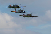Six Hawker Hurricanes fly in formation around the airfield and then come into land - Duxford Battle of Britain Air Show taking place during IWM (Imperial War Museum) Duxford's centenary year. Duxford's principle role as a Second World War fighter station is celebrated at the Battle of Britain Air Show by more than 40 historic aircraft taking to the skies.