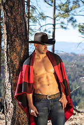 shirtless muscular cowboy with a blanket over his shoulders outdoors in the woods