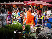 "05 APRIL 2014 - BANGKOK, THAILAND:   A Buddhist monk walks through Khlong Toey Market in Bangkok. Khlong Toey (also called Khlong Toei) Market is one of the largest ""wet markets"" in Thailand. The market is located in the midst of one of Bangkok's largest slum areas and close to the city's original deep water port. Thousands of people live in the neighboring slum area. Thousands more shop in the sprawling market for fresh fruits and vegetables as well meat, fish and poultry.     PHOTO BY JACK KURTZ"