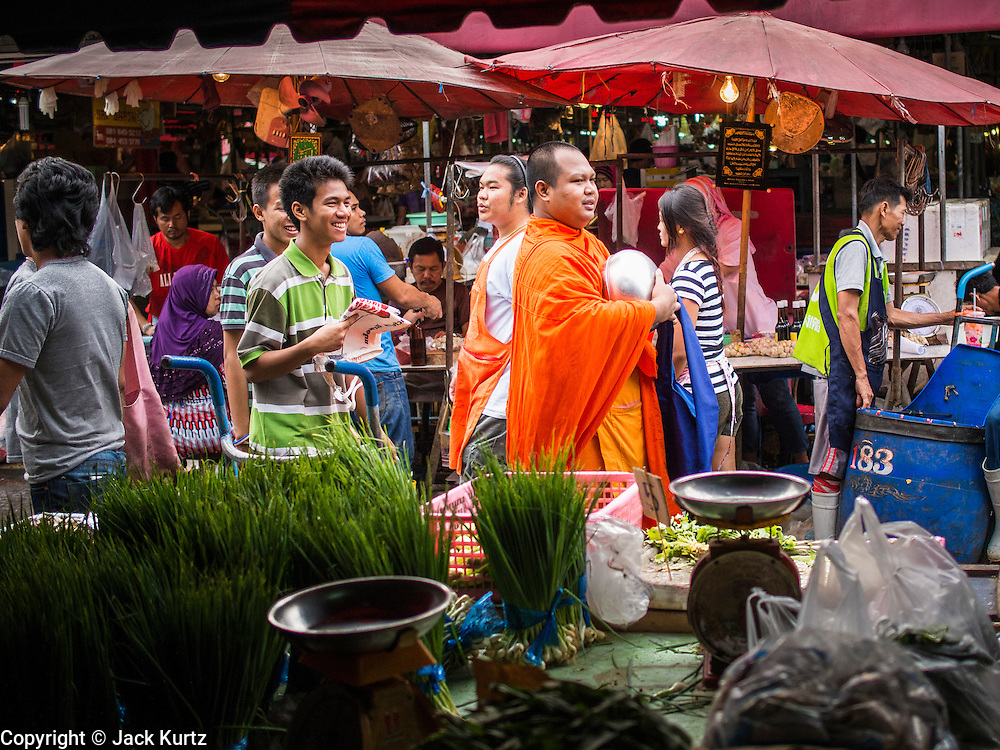 """05 APRIL 2014 - BANGKOK, THAILAND:   A Buddhist monk walks through Khlong Toey Market in Bangkok. Khlong Toey (also called Khlong Toei) Market is one of the largest """"wet markets"""" in Thailand. The market is located in the midst of one of Bangkok's largest slum areas and close to the city's original deep water port. Thousands of people live in the neighboring slum area. Thousands more shop in the sprawling market for fresh fruits and vegetables as well meat, fish and poultry.     PHOTO BY JACK KURTZ"""