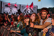 People dancing in front of Shepard Fairey Obey posters in the Hell arena, Shangri La field, Glastonbury Festival 2016. The Glastonbury Festival is the largest greenfield festival in the world, and is now attended by around 175,000 people. Its a five-day music festival that takes place near Pilton, Somerset, United Kingdom. In addition to contemporary music, the festival hosts dance, comedy, theatre, circus, cabaret, and other arts. Held at Worthy Farm in Pilton, leading pop and rock artists have headlined, alongside thousands of others appearing on smaller stages and performance areas.