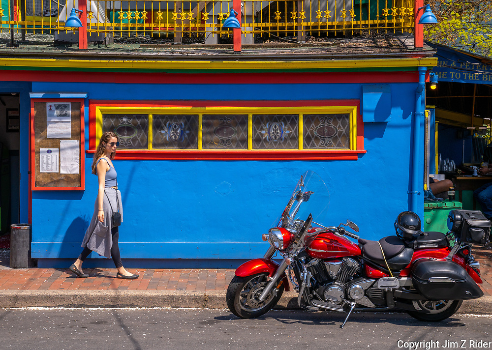 A young woman admires a Yamaha V Star as she strolls past the iconic John and Peter's bar in New Hope, PA, a regional tourist destination along the Delaware River with a wide variety of unique shops, galleries, bars, and restaurants.