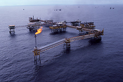 Stock photo of a complex of offshore oil production platforms with gas flare burning off waste gas off of the coast of Brunei in the South China Sea.