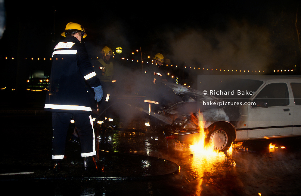 As flames ignite under the engine, firefighters attend a car fire in central London. A Ford car has caught fire in its engine compartment during the evening and firemen have been called to attend. With the bonnet open, fire is still seen beneath the engine and near front tyres where fuel and oil may be ready to ignite too. Pointing a hose into the seat of the fire, a firefighter sprays a pressured jet of water into the affected area.