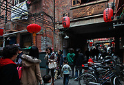 Visitors and shoppers walk through the narrow alley of Tianzifang in Shanghai, China on 09 November, 2011. Once a crowded old neighborhood located in the heart of Shanghai's former French concession, Tianzifang is now a popular tourist and leisure spot with a tightly knit group of restaurants, cafes, and shops.