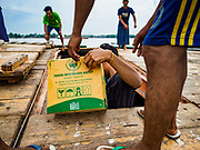 22 NOVEMBER 2017 - YANGON, MYANMAR: Workers store Burmese liquor in the hold of a cargo ship taking the liquor up the Irrawaddy River. Myanmar's road system lags behind its neighbors in Southeast Asia and a lot of cargo is still moved by ships and barges.    PHOTO BY JACK KURTZ