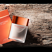 A studio product pack shot of Clinique happy for Men aftershave shave balm. Photographed on a rough wooden background to contrast the smooth texture of the product.