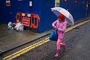 Wet day on Brick Lane in the East End of London, UK. A young girl wearing pink clothes and using an umbrella walks on the rain covered road past a construction site hoarding.