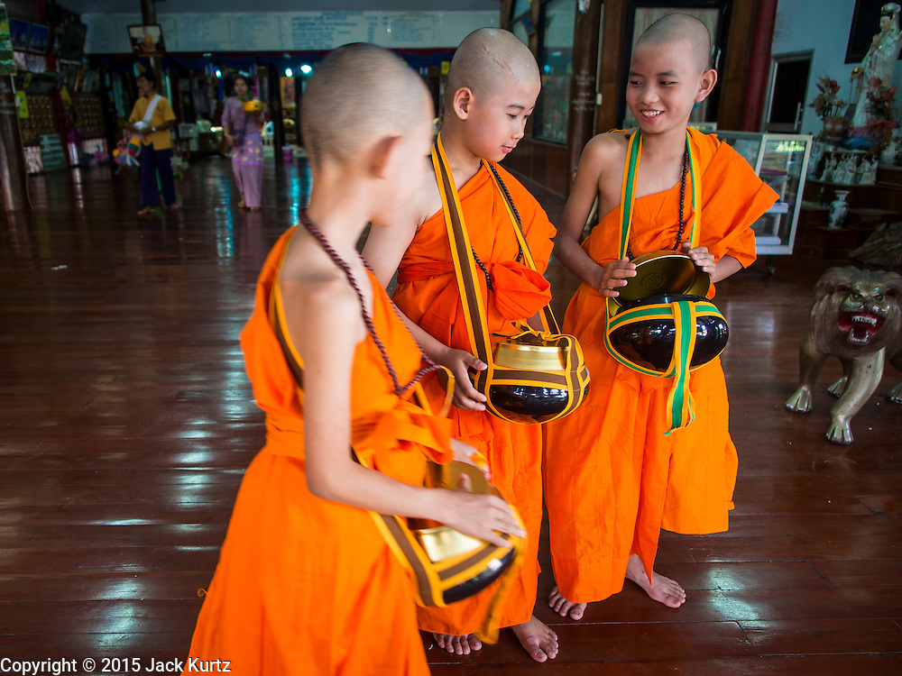 """06 APRIL 2015 - CHIANG MAI, CHIANG MAI, THAILAND: Newly ordained Buddhist novices leave the """"viharn,"""" or prayer hall, after their ordination on the last day of the three day long Poi Song Long Festival in Chiang Mai. The Poi Sang Long Festival (also called Poy Sang Long) is an ordination ceremony for Tai (also and commonly called Shan, though they prefer Tai) boys in the Shan State of Myanmar (Burma) and in Shan communities in western Thailand. Most Tai boys go into the monastery as novice monks at some point between the ages of seven and fourteen. This year seven boys were ordained at the Poi Sang Long ceremony at Wat Pa Pao in Chiang Mai. Poy Song Long is Tai (Shan) for """"Festival of the Jewel (or Crystal) Sons.   PHOTO BY JACK KURTZ"""