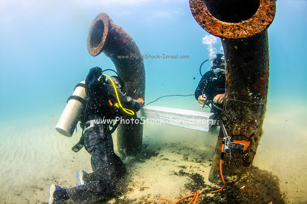 Commercial divers attach a zinc anode to a brine discharge pipe from a desalination plant on the seabed to a distance of 300 meter from the shore. Zinc anodes are attached to underwater metal parts to reduce corrosion. Brine discharge can have a negative impact on the ocean ecosystem. Photographed in Israel Mediterranean sea. Photographed in the Mediterranean Sea, Israel