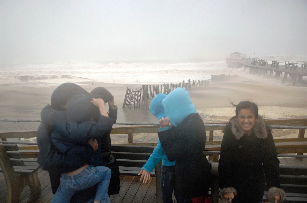 Onlookers brace themselves against the strong winds along the boardwalk in Ocean Grove during the dangerous conditions of Hurricane Sandy on October 29. Hurricane Sandy continued on its path Monday, forcing the shutdown of mass transit, schools and financial markets, sending coastal residents fleeing for higher ground, and threatening a dangerous mix of high winds and soaking rain.