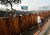 Gilroy resident Chris Martinez talks on his cell phone as he hoses off his fence in attempt to ward away fire on August 6, 2004...Photo by Max Morse