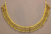 Gold strap necklace with seed-like pendants 330-300 BC Said to be from Melos. This necklace with its festoon of pendants enhanced with blue and green enamel, was repaired by Alessandro Castellani in about 1870: his restorations can be identified by the techniques used and by the way in which his elements have discoloured.