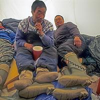 BAFFIN ISLAND, Nunavut, Canada. Inuit hunters sit out a storm in a tent, catching up on regional gossip on a short-wave radio.  (L to R: Laimakie Palluq, Jushua Illuaq & Joannasie Apak).