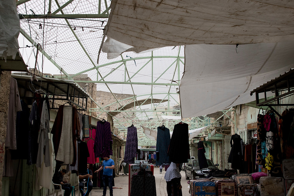 Illegal Israeli settlers in the city often throw rocks, rubbish and even urine down on Palestinians in the market. The souk is now covered with a protective roof to protect shoppers and traders