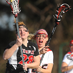 Temple junior midfielder Stephany Parcell cradles the ball away from Rutgers freshman defender Hollie DiMuro. Temple defeated Rutgers 12-11 in NCAA women's college lacrosse at the Rutgers Turf Field in Piscataway, N.J.