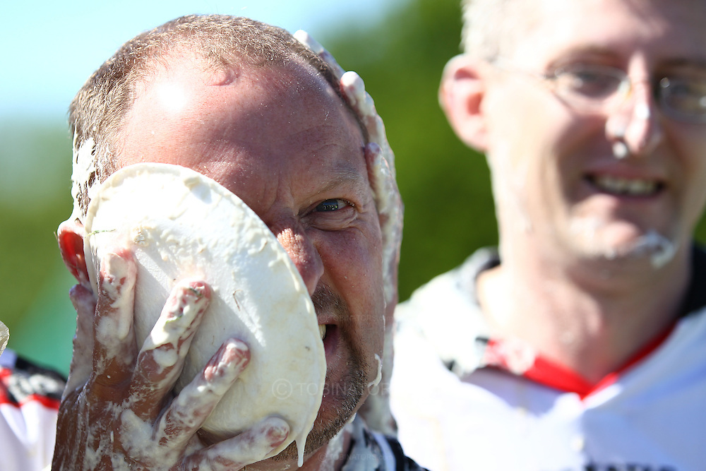 Coxheath, Kent - Saturday, May 22nd 2010: A contestant in the Coxheath team is pied by a colleague after they lost 96-56 in the final at the World Custard Pie Championships at Coxheath near Maidstone, Kent. The first championship was held in 1967 in Coxheath using a special custard recipe developed by Richard Hearn aka Mr Pastry. The championship is made up of teams competing in heats, semi finals and the final, with the number of pies available per team increasing from 5 in the heats to 10 in the final. 6 points are scored for a direct hit on the face, 3 points for the shoulders or upwards, 1 point for any other part of the body, and points are deducted for misses. A discretionary 5 points can be awarded for the most amusing and original throwing technique. The event is part of the Rotary Club funday. (Pic by Andrew Tobin/SLIK Images)