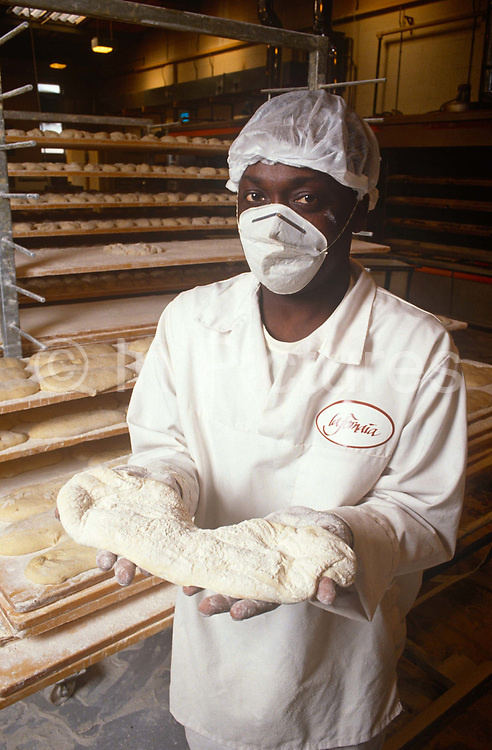 """A portrait of a baker holding yet to be baked dough for Ciabatta bread. Standing by trays of ready to bake loaves, the man is of African or afro-Caribbean origin, clearly made out in the white of his uniform and mix, his white baker's uniform's sleeves also spattered with flour. Ciabatta (literally """"carpet slipper"""") is an Italian white bread made with wheat flour and yeast. The loaf is somewhat elongated, broad and flattish. Its name is the Italian word for slipper. There are many variations of ciabatta. Ciabatta in its modern form was developed in 1982. Since the late 1990s it has been popular across Europe and in the United States, and is widely used as sandwich bread."""