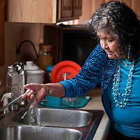 100814       Cable Hoover<br /> <br /> Mary Beach checks the faucet in her kitchen after water was hooked up in her house in Navajo Wednesday.
