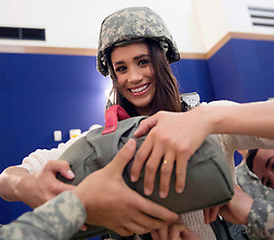 Actress Meghan Markle is shown how to wear a parachute by the soldiers of the 173rd Airborne Brigade during a holiday visit to service members December 7, 2014 in Vicenza, Italy. The USO tour is for service members deployed outside of the United States during the holidays.