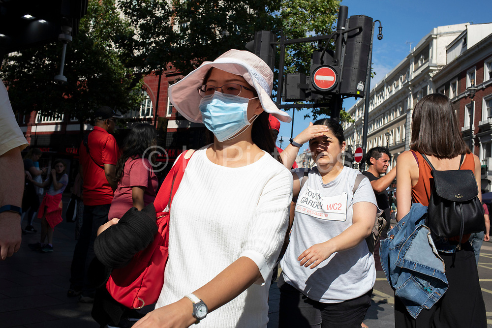 Asian woman wearing an environmental anti-pollution mask as protection for herself from breathing in air pollution in London, United Kingdom.