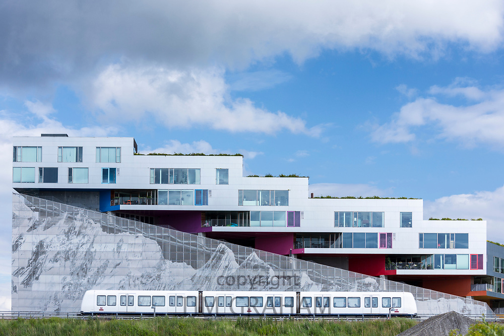 Ultra-modern new apartments with mural of mountain range below and train on Orestads Boulevard, Copenhagen, Denmark