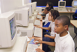 Primary school children working at computers in IT lesson,