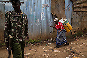 A woman walks past a soldier on duty inside Kibera Slum, Nairobi. Considered to be the largest slum in Africa with a population close to 1 million people. The living conditions in it  are considered of extreme poverty with most housholds having no runing water or sanitation. The population is made up of all ethno-linguistic groups of Kenya drawing many residents from the poorest rural backgrounds.